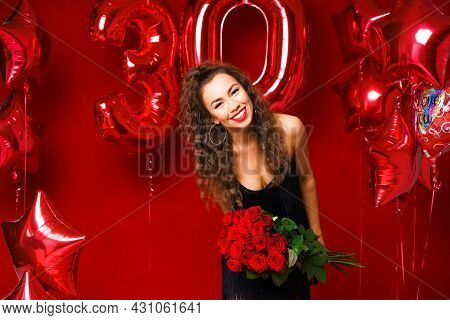 Beautiful Young Woman On A Red Background With Red Balloons And A Bouquet Of Red Roses. Cheerful And