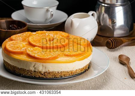 Side View Of Delicious Homemade Orange Cheesecake Garnished With Pieces Of Ripe Orange In White Cera