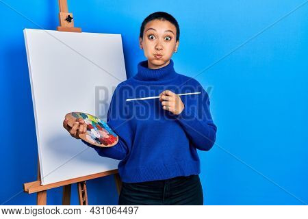Beautiful hispanic woman with short hair holding paintbrush and palette puffing cheeks with funny face. mouth inflated with air, catching air.