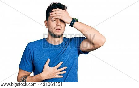 Young hispanic man wearing casual t shirt touching forehead for illness and fever, flu and cold, virus sick