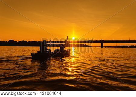 Silhouettes Of People In Kayak At Sunset. Young Married Couple Is Boating On River. Concept Of Outdo