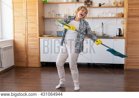 A Woman With A Mop Cleans The Kitchen.