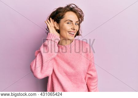 Young brunette woman wearing casual winter sweater smiling with hand over ear listening and hearing to rumor or gossip. deafness concept.
