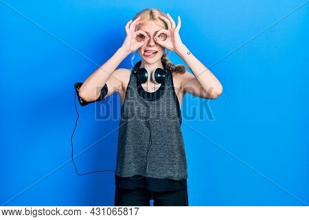 Beautiful caucasian woman with blond hair wearing sportswear doing ok gesture like binoculars sticking tongue out, eyes looking through fingers. crazy expression.