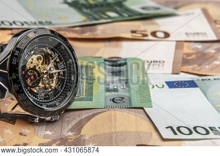 Time Is Money.a Beautiful Mechanical Watch In Close-up Lies On The Euro Money.manual Counting Of Eur
