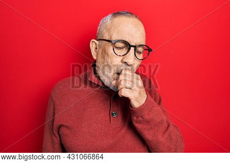 Handsome mature man wearing casual sweater and glasses feeling unwell and coughing as symptom for cold or bronchitis. health care concept.