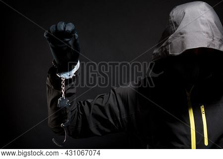 Closeup View Of The Hands Of A Burglar Or Hucker In Black Gloves With Handcuffs On A Black Backgroun
