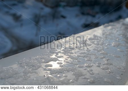 Spring Drops And Melting Snow On The Windowsill Outside The Plastic Window In Evening, Closeup. Off-