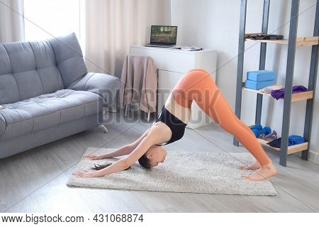 Young Woman In Sportswear Is Practicing Yoga Doing Upward Nd Downward Facing Dog Pose In Flow On Car