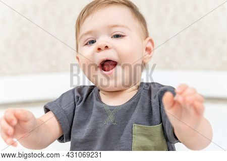 Portrait Of Laughing Baby Sitting On Bed Looking At Camera. Happy Little Child Baby Boy Playing At H