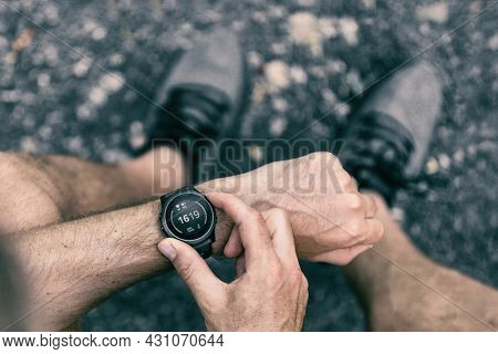 Smartwatch wearable smart tech fitness active athlete man using sports watch on exercise cardio workout checking his heart rate. City street with grey running shoes.