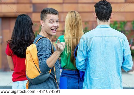 Laughing German Male Student With Group Of Other Students At Campus Of University