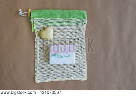 Natural Handmade Soap On Mesh Packaging Bag And Souvenir Stone Heart On Craft Paper. Hygiene, Body C