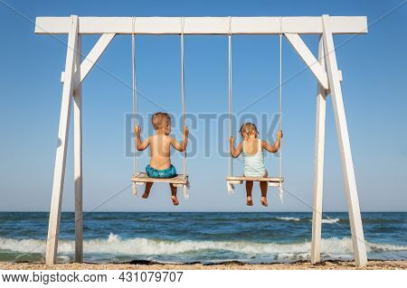 Back View Couple Of Cute Little Adorable Small Caucasian Sibling Kids Enjoy Having Fun Swinging And
