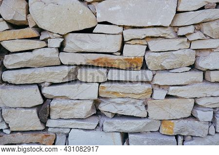 Sandstone Masonry Texture. Retaining Wall Lined With Sandstone Stones. Natural Stone Background.