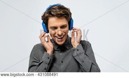 Joyful Guy In Grey Shirt Listening Music Wearing Blue Wireless Headphones Enjoying Sound With Closed
