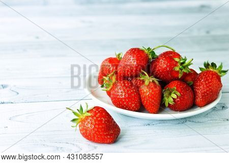 Plate With Red Fresh Strawberry On Light Table.