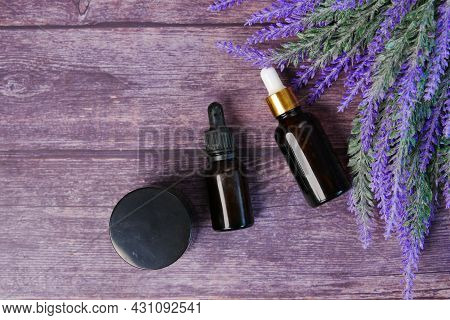 Essential Lavender Oil And Flowers On Table With Copy Space