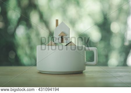 Miniature Wooden Home Placed On The White Ceramic Cup. Home Care, Home For Sale Concept.