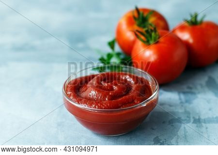Tomato Paste Or Sauce In Glass Bowl With Red Tomatoes And Parsley On Gray Concrete Background