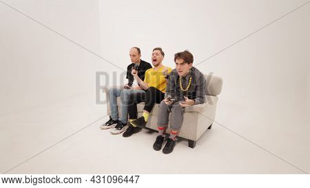 Happy Winning While Gaming Guy In Yellow Shirt Playing Video Games With Friends Sitting On A White S