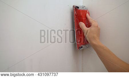 Plasterer Smooths The Walls With Sandpaper Close-up. Male Hand Of A Worker. Sanding The Walls Close-