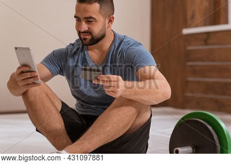 Fitness Trainer Man With Smartphone And Debit Or Credit Card Buying Online Equipment Or Doing Sport