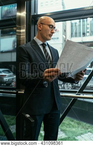 Business Man Looking At Papers Next To The Window. Businessman Looking At Documents Wearing A Suit S