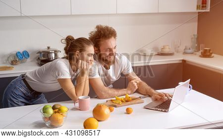 Young Couple Cooking Healthy Food In Kitchen At Home. Girl Leaned On Man Smiling Watching Romantic M