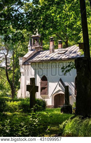 Vertical Photo Of White Chapel And Churchyard Graveyard Surrounded With Green Trees. Peaceful Scener