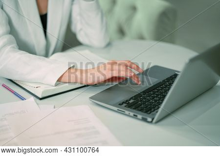 No Face Visible Businesswoman Working Sitting In Front Of Laptop Wearing White Official Suit. Office