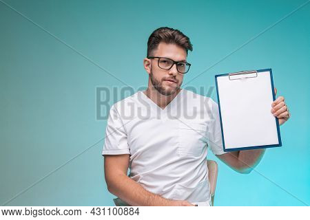 Male Physician Practitioner In Glasses Showing Blank Space Sheet For Doctor Report On Blue Backgroun