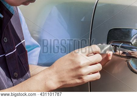 Close-up Of Person's Young Man Locksmith Hand Opening Bronze Car Door With Lock Picker. Locksmith Do