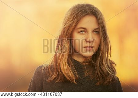 Happy young girl in black pullover walking outdoor