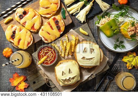 Halloween Party Food Corner Table Scene Over A Wood Background. Halloween Party Burger, Mummies Mini