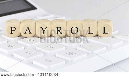 Wooden Cubes With Text Payroll On The Calculator, Business