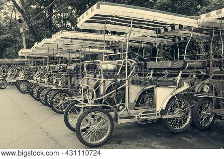 Row Of Vintage Pedal-power Four-wheeled Surrey Bike For Rent On Parking In Public Park. Rental Stati