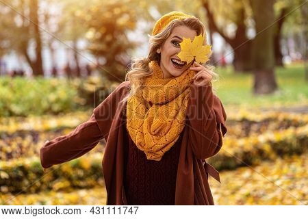 Happy Laughing Woman Hide Eye With A Yellowed Leaf In Yellow Knitted Beret With Autumn Leaves In Han