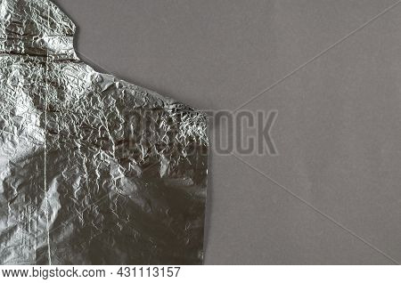 Crumpled Foil Against A Gray Background. Roll Of Aluminum Foil For Food Packaging With An Uneven Tor