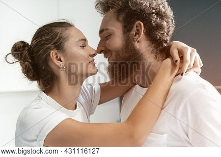Romantic Couple In Love. Close Up Portrait. Young Man Kissing His Wife Standing At The Kitchen. Morn