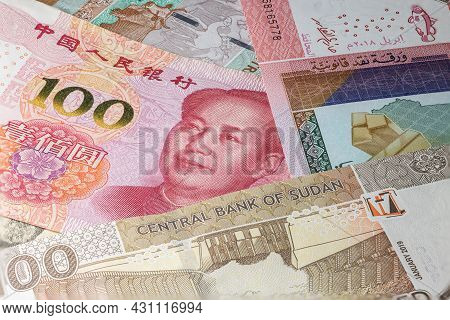 Close Up To 100 Yuan Of The People Republic Of China Between Sudanese Pounds Banknotes. 50 Pound Ban