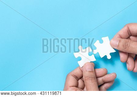 Hand Push A Piece Of Jigsaw Puzzle To Complete The Mission For Business Merging Concept Or Coorperat
