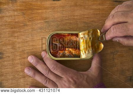 Opening A Can Of Sardines. Man Hands Opening A Can Of Preserves With Sardines In Tomato