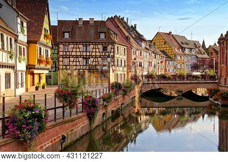 Colmar, France, Late Day View With Half Timbered Houses, Flowers, Bridge And Reflections In The Beau