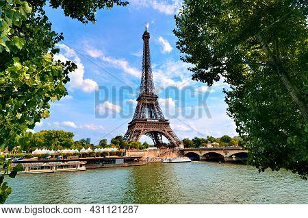 Eiffel Tower, Iconic Paris Landmark Across The River Seine With Green Leaves Vibrant Blue Sky, Franc