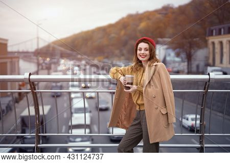 Portrait Of A Pretty Smiling French Young Woman Looking At Camera Standing At Pedestrian Bridge With