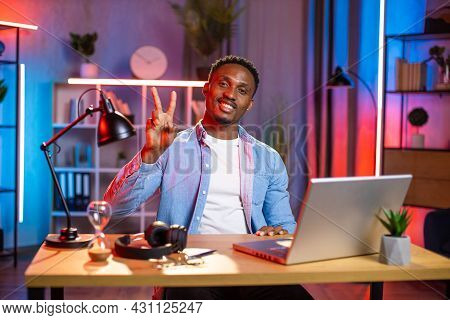 Handsome African Man Sitting At Table With Modern Laptop And Gesturing Peace Sign With Fingers. Happ
