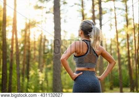 A Sportive Girl Stands In The Forest Before A Fitness Class And Looks Towards The Sun. View From The