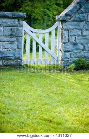 White Garden Gate In Stone Fence