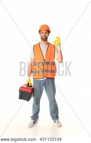 Smiling Repairman Holding Toolbox And Showing Ok On White Background